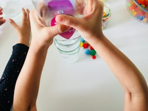 my toddler putting some oil into the a close up of the items you can put in Sensory calm down bottles