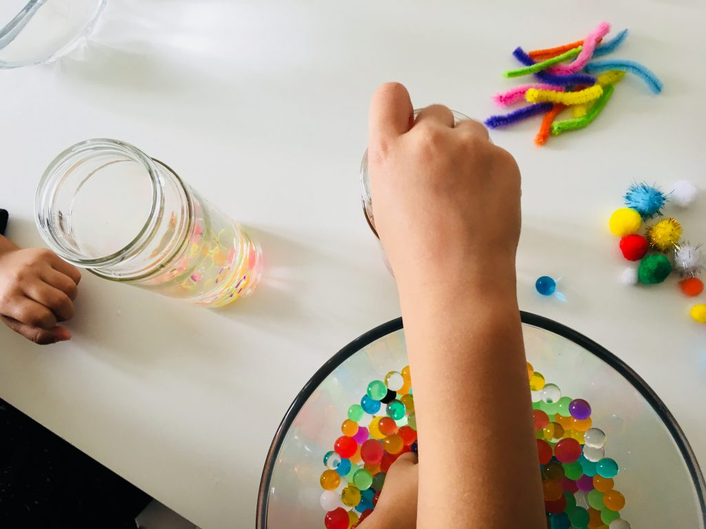 adding pom poms and other items to our adding some loom bands to our my toddler putting some oil into the a close up of the items you can put in Sensory calm down bottles