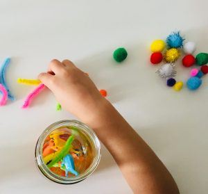adding pipe cleaners to our my toddler putting some oil into the a close up of the items you can put in Sensory calm down bottles