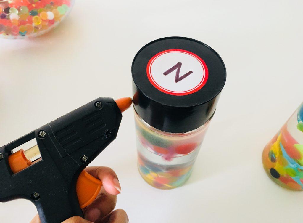 using a glue gun to seal the sensory calm down bottles